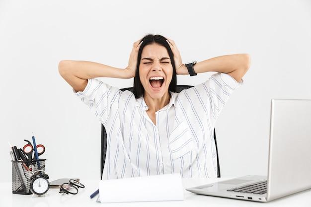 Atractiva joven empresaria molesta sentada en el escritorio aislado sobre la pared blanca, gritando