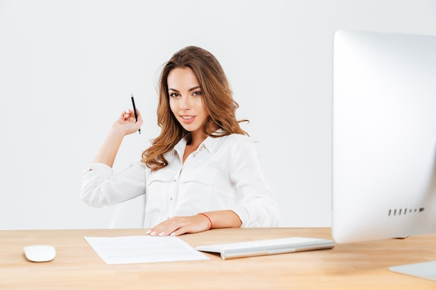 Atractiva joven empresaria sosteniendo la pluma mientras está sentado en el escritorio de la oficina con el portátil