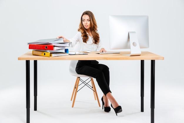 Atractiva joven empresaria trabajando con documentos mientras está sentado en la mesa isoltaed sobre el fondo blanco.
