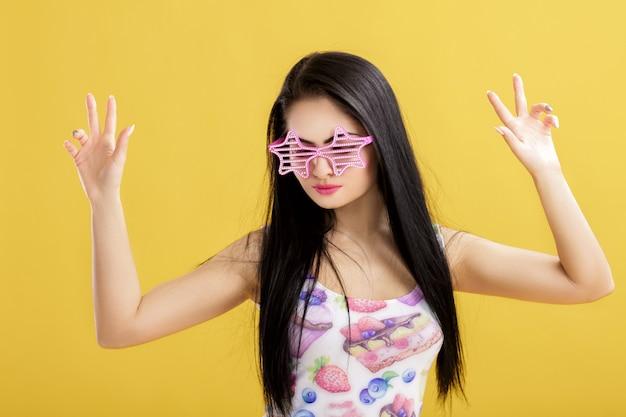 Atractiva joven morena en camiseta rosa sin mangas en amarillo mujer divertida con gafas de sol rosa bailando