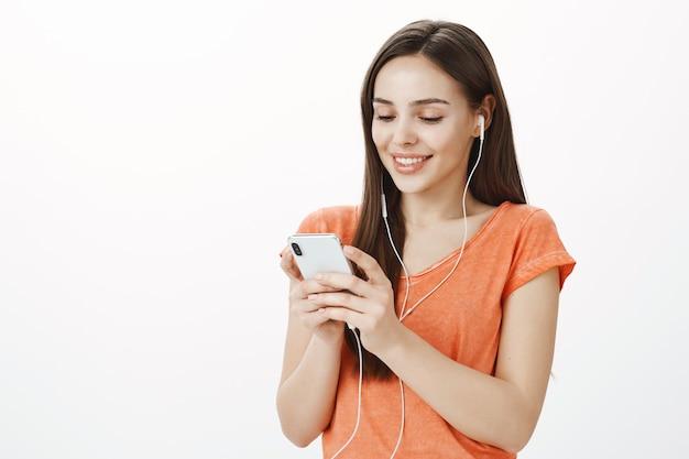 Atractiva joven morena escuchando música en auriculares y enviando mensajes de texto, usando el teléfono móvil, disfrutando de un interesante podcast