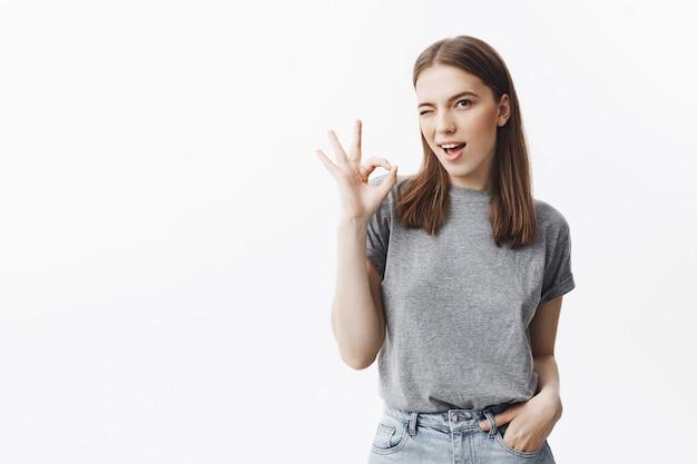 Atractiva joven morena europea con ojos marrones en ropa gris, guiñando un ojo, mostrando un gesto ok con la mano, sosteniendo la mano en el bolsillo, siendo feliz y relajado.
