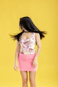 Atractiva joven morena en falda rosa y camiseta sin mangas en amarillo mujer divertida