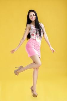 Atractiva joven morena en falda rosa y camiseta sin mangas en amarillo