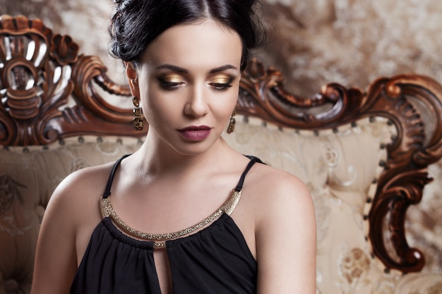 Atractiva joven morena sentada en un hermoso sofá, retrato de primer plano, sombra de ojos dorada