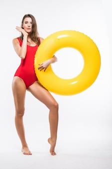 Atractiva joven mujer sexy en traje de baño rojo tiene colchón de aire amarillo redondo aislado sobre fondo blanco