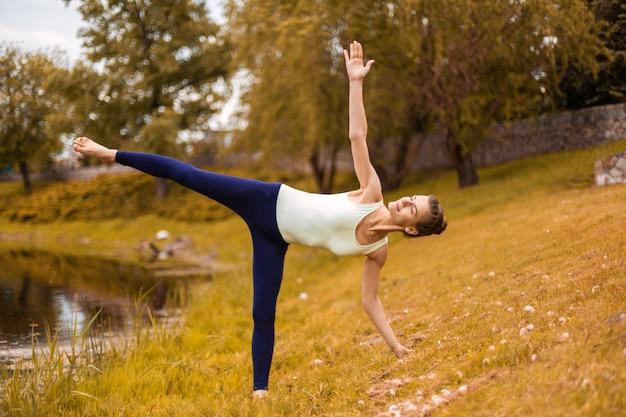 Atractiva joven mujer yogui practicando yoga haciendo ejercicio utthita trikonasana