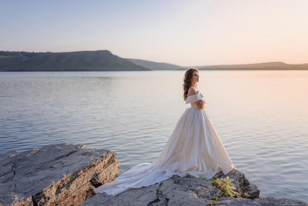 Atractiva joven novia caucásica está de pie al borde de un acantilado cerca del mar