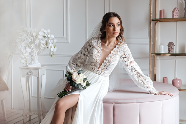 Una atractiva joven novia con un hermoso vestido de novia boho posando con un ramo de flores en una habitación luminosa.