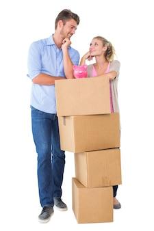 Atractiva joven pareja apoyándose en cajas con hucha