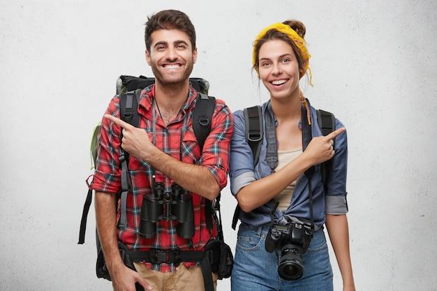 Atractiva joven pareja aventurera enamorada, vestida con ropa práctica, con mochilas, cámara fotográfica y binoculares con una apariencia alegre, apuntando con los dedos en direcciones opuestas