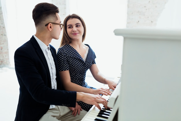 Una atractiva joven pareja tocando el piano mirando el uno al otro