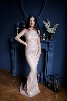 Atractiva joven está de pie en un lujoso vestido largo beige sobre el fondo azul con chimenea