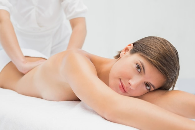 Atractiva joven recibiendo masaje de espalda en el spa