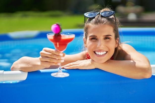 Una atractiva joven relajándose en la piscina en el patio trasero