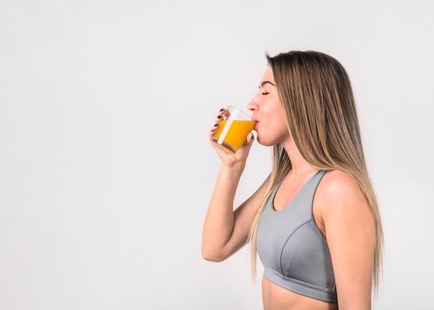 Atractiva joven en ropa deportiva bebiendo jugo
