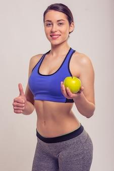 Atractiva joven en ropa deportiva está sosteniendo una manzana.