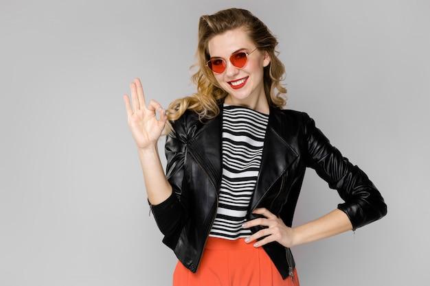 Atractiva joven rubia en blusa a rayas y chaqueta de cuero sonriendo en gafas de sol con las manos en la cintura de pie