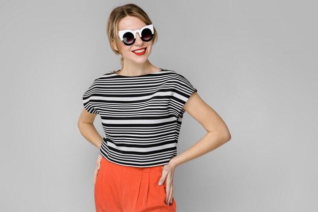 Atractiva joven rubia en blusa a rayas sonriendo en gafas de sol con las manos en la cintura en gris