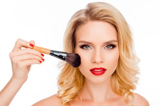 Atractiva joven rubia con labios rojos aplicando polvo con pincel