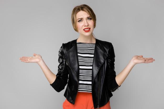 Atractiva joven rubia perpleja en blusa a rayas y chaqueta de cuero de pie en la pared gris