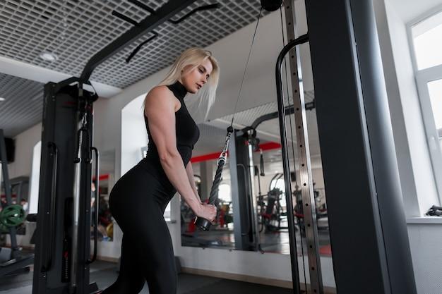 Atractiva joven rubia en ropa deportiva haciendo ejercicios de fuerza para las manos con la ayuda del simulador moderno en el gimnasio