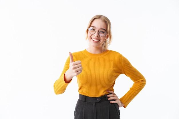 Atractiva joven rubia vistiendo suéter que se encuentran aisladas sobre la pared blanca, pulgares arriba