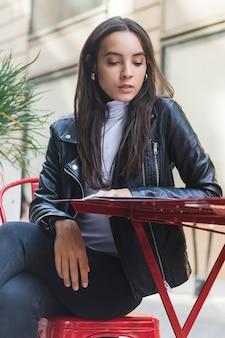 Una atractiva joven sentada en un café al aire libre leyendo la tarjeta de menú