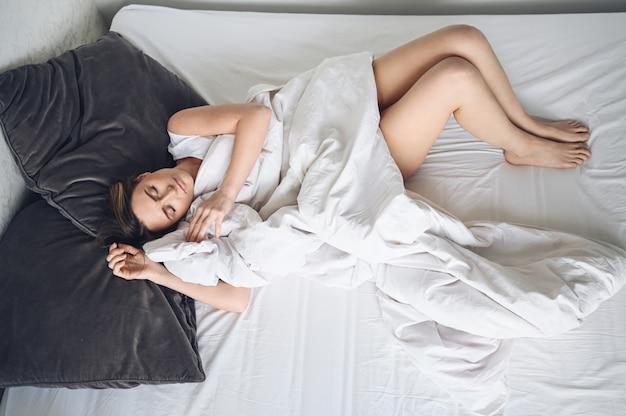 Atractiva joven sonriente que se extiende en la cama despertando solo, feliz concepto, despierto después de un sueño saludable en una cómoda cama cómoda y un colchón disfrutan de buenos días