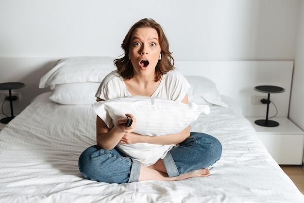 Atractiva joven sorprendida sentada en la cama en casa viendo la televisión