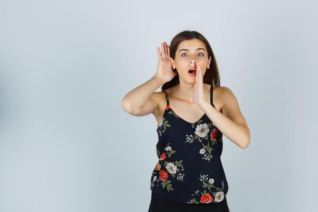 Atractiva joven sosteniendo la mano cerca de la boca mientras escucha el secreto en la blusa y mira sorprendida, vista frontal.