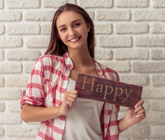 Atractiva joven está sosteniendo una placa de madera
