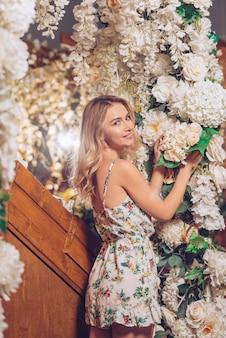 Una atractiva joven tocando flores blancas cerca de la decoración de flores