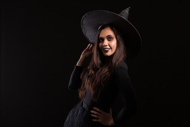 Atractiva joven vestida como una bruja para halloween con un gran sombrero sonriendo. bruja malvada.