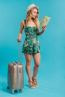 Atractiva joven en vestido y sombrero con mapa y maleta