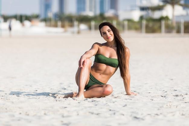 Una atractiva joven vistiendo bikini se sienta en una playa
