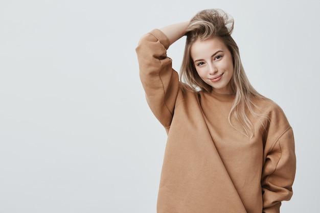Atractiva joven vistiendo elegante sudadera de manga larga y posando