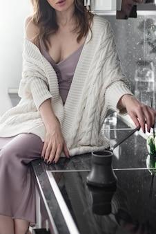 Atractiva joven vistiendo suéter blanco de punto se sienta en la mesa de la cocina haciendo café preparado en la mañana