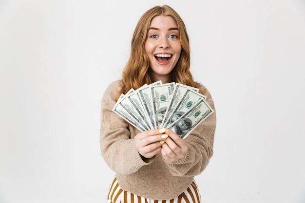 Atractiva joven vistiendo suéter que se encuentran aisladas sobre una pared blanca, mostrando billetes de dinero, celebrando
