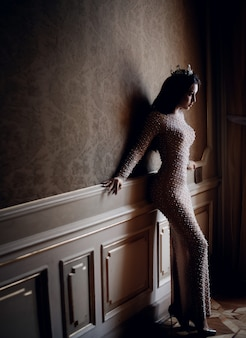 Atractiva jovencita vestida con un vestido de noche beige cerca de la pared con un cuerpo perfecto
