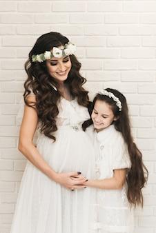 Atractiva mamá embarazada con su hija esperando al bebé. fotos de embarazo en las últimas semanas.