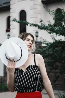 Atractiva modelo femenina sensual en un top de rayas y pantalones rojos de vacaciones con un sombrero en el jardín