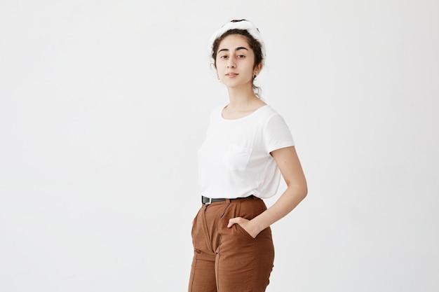 Atractiva modelo de mujer joven con cabello oscuro y ondulado en moño, con camiseta y pantalones blancos, manteniendo las manos en los bolsillos, posando contra la pared blanca con espacio de copia para publicidad