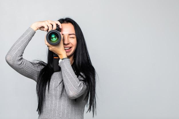 Atractiva morena apunta su cámara. componer una fotografía en estudio, aislado en la pared gris