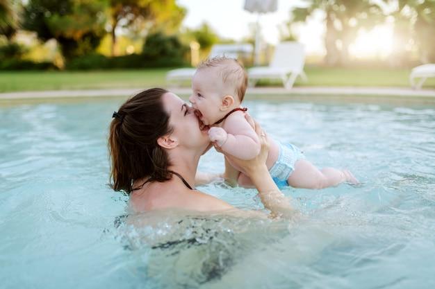 Atractiva morena caucásica dedicada besando a su amoroso hijo de 6 meses mientras está de pie en la piscina. primera vez en concepto de piscina.