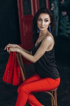 Atractiva morena en traje rojo se sienta en la silla vieja en estudio oscuro