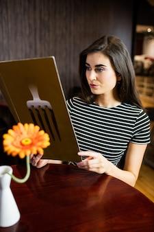 Atractiva morena revisando el menú en el bar