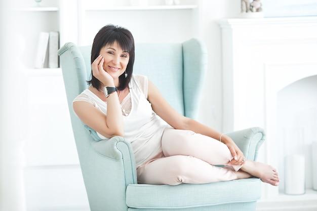 Atractiva mujer adulta sentada en el sofá en el interior. hermosa mujer de mediana edad en casa.