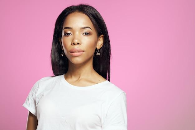 Atractiva mujer africana pelo largo decoración rosa fondo