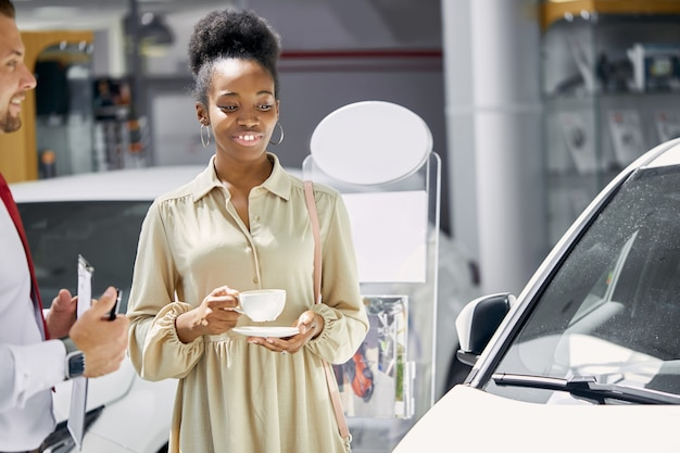 Atractiva mujer afro joven disfruta de ser propietario de un auto nuevo